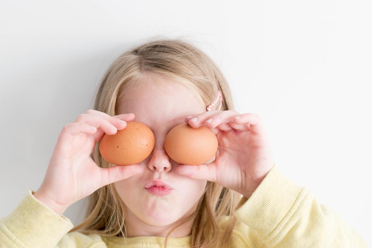young girl holding up eggs in front of her eyes