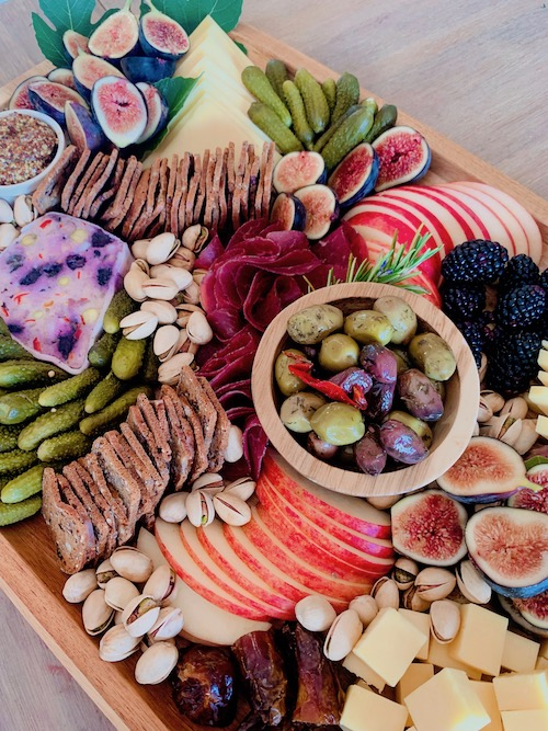 display of sliced meats, cheeses, fruits and condiments on a board