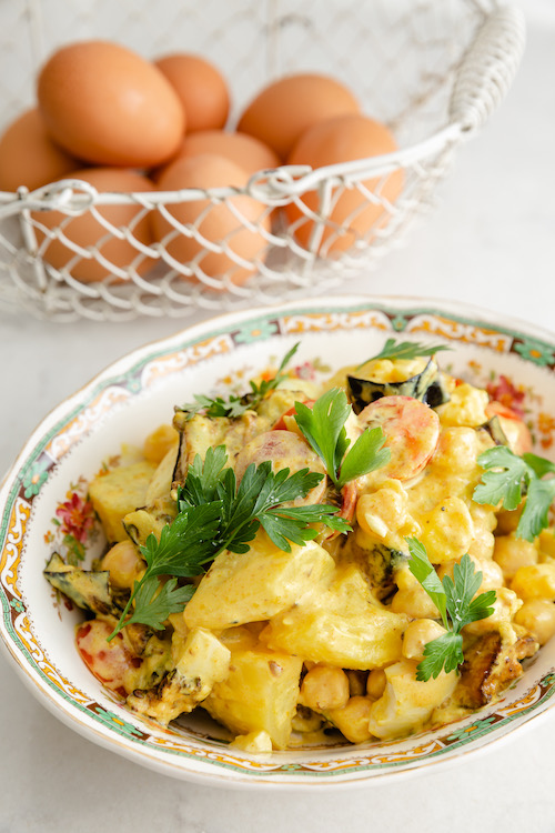 Sabich salad with eggplant, potatoes and boiled eggs in a decorative dish
